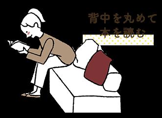 背中を丸めて本を読む
